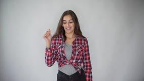 Retrato do divertimento de rir a jovem mulher atrativa com gesto do telefone à disposição que ri da câmera, no fundo cinzento video estoque