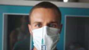 Retrato do doutor caucasiano masculino novo na máscara que derrama um líquido de uma seringa Trabalhador médico que prepara a ser vídeos de arquivo