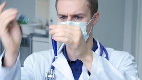 Retrato do doutor caucasiano masculino novo que derrama um líquido azul de uma seringa a um tubo, video estoque