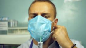Retrato do doutor caucasiano masculino novo que derrama um líquido de uma seringa, descolando seus máscara protetora e pensamento video estoque