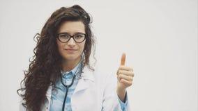 Retrato do doutor de sorriso novo feliz da menina Vestido em uma veste branca Estando lisa, uma mão põe a direito dentro vídeos de arquivo