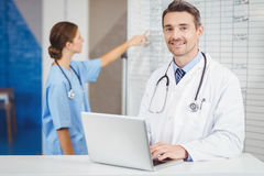 Retrato do doutor de sorriso que trabalha no portátil com o colega que aponta na carta Imagem de Stock Royalty Free