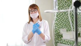 Retrato do doutor fêmea bonito na máscara asséptica da boca que olha a câmera haqppily Mulher que limpa suas mãos no azul video estoque