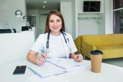 Retrato do doutor fêmea de sorriso novo que faz anotações no caderno ao sentar-se atrás da tabela com telefone e café para dentro imagens de stock royalty free