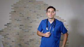 Retrato do doutor masculino considerável com phonendoscope no pescoço que sorri e que levanta 4K video estoque
