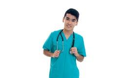 Retrato do doutor masculino moreno novo alegre no uniforme com levantamento do estetoscópio isolado no fundo branco Fotografia de Stock Royalty Free