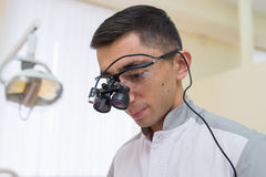 Retrato do doutor novo com as lupas binoculares dentais em sua cara na clínica do dentista Fotografia de Stock Royalty Free