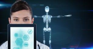 Retrato do doutor que mostra ícones médicos no PC da tabuleta com o esqueleto no fundo Imagens de Stock