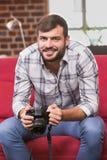 Retrato do editor de fotos ocasional que guarda a câmera Fotografia de Stock