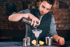 Retrato do empregado de bar que derrama o margarita fresco do cal no vidro no restaurante Fotografia de Stock Royalty Free