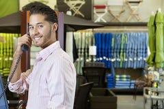 Retrato do empregado novo considerável na loja que escuta o receptor de telefone Imagens de Stock Royalty Free
