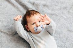 Retrato do encontro irritado, furioso, olhando de sobrancelhas franzidas e agressivo do bebê em uma cama As emo fotos de stock