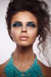 Retrato do estúdio da beleza da mulher sol-bronzeada com azul brilhante e foto de stock royalty free