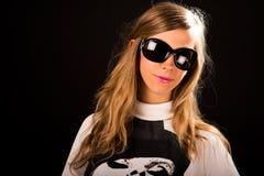 Retrato do estúdio da jovem mulher no fundo preto com óculos de sol Foto de Stock