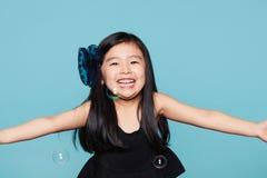 Retrato do estúdio da menina asiática com bolhas de sabão na frente do fundo azul Imagem de Stock Royalty Free