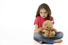 Retrato do estúdio da menina infeliz com urso da peluche Fotografia de Stock