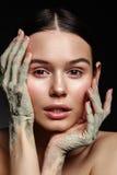 Retrato do estúdio da mulher bonita com máscara da mão da lama em b preto imagem de stock