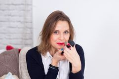Retrato do estúdio da mulher de negócio nova sensual com cabelo louro e os bordos completos 'sexy' que põem o batom vermelho que  fotografia de stock royalty free