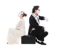 Retrato do estúdio de dois mimes que sentam-se na mala de viagem Fotografia de Stock Royalty Free