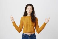 Retrato do estúdio de meditar fêmea magro novo expressivo, mãos de espalhamento com gesto do zen, sendo calmo ao estar imagem de stock