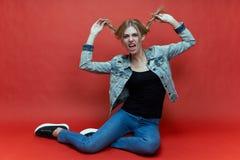 Retrato do estúdio de um adolescente fêmea novo na roupa ocasional a careta brincalhão da expressão fotos de stock royalty free