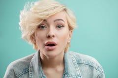 Retrato do estúdio de uma menina loura atrativa nova que canta a música fotografia de stock