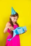 Retrato do estúdio de uma menina que veste um chapéu do partido em seu aniversário Menina bonito aberta sua caixa de presente do  foto de stock