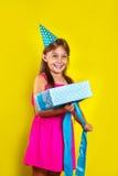 Retrato do estúdio de uma menina que veste um chapéu do partido em seu aniversário Menina bonito aberta sua caixa de presente do  imagem de stock