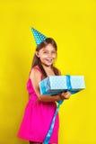 Retrato do estúdio de uma menina que veste um chapéu do partido em seu aniversário Menina bonito aberta sua caixa de presente do  imagens de stock