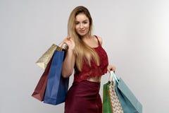 Retrato do estúdio no fundo isolado de uma jovem mulher com cabelo longo Realiza em dois pacotes e sacos de compras da cor das mã foto de stock
