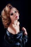 Retrato do estúdio da mulher loura com o revestimento de couro do motociclista olhar Imagens de Stock