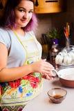 Retrato do estilo de vida da jovem mulher feliz que cozinha o peru e os vegetais para o jantar da ação de graças Imagens de Stock Royalty Free