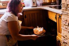 Retrato do estilo de vida da jovem mulher feliz que cozinha o peru e os vegetais para o jantar da ação de graças Imagem de Stock