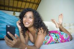Retrato do estilo de vida da mulher americana nova do africano negro feliz e bonito em casa que usa trabalhos em rede e te do tel foto de stock