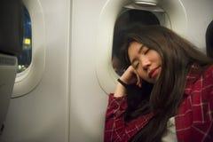 Retrato do estilo de vida da mulher coreana asiática bonita e doce nova do turista que dorme no plano durante o voo longo que sen imagens de stock