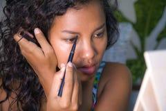 Retrato do estilo de vida da mulher latino-americano feliz e bonita nova que usa o desenho de lápis da sobrancelha o contorno que fotografia de stock