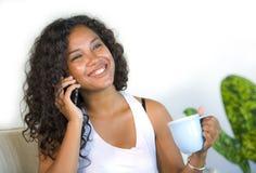 Retrato do estilo de vida da mulher latino-americano preta feliz e lindo nova que fala no sofá e do sofá da sala de visitas do te fotos de stock royalty free