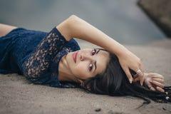 Retrato do estilo de vida de uma morena da mulher no fundo do lago que encontra-se na areia em um dia nebuloso Romântico, delicad Imagem de Stock