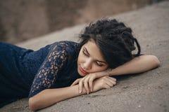 Retrato do estilo de vida de uma morena da mulher no fundo do lago que encontra-se na areia em um dia nebuloso Romântico, delicad Fotografia de Stock