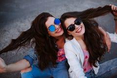 Retrato do estilo de vida do verão de duas mulheres à moda do moderno com corpo 'sexy' do ajuste, o equipamento vestindo da sarja Imagem de Stock Royalty Free