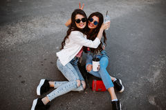 Retrato do estilo de vida do verão de duas mulheres à moda do moderno com corpo 'sexy' do ajuste, o equipamento vestindo da sarja Foto de Stock