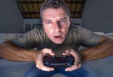 Retrato do estilo de vida dos jovens forçados e do homem entusiasmado do gamer que joga a sala de visitas do jogo de vídeo em cas fotos de stock royalty free