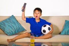 Retrato do estilo de vida em casa de anos do menino idoso dos jovens 7 ou 8 que guarda a bola de futebol que olha o jogo de futeb fotografia de stock