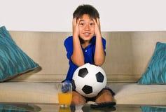 Retrato do estilo de vida em casa de anos do menino idoso dos jovens 7 ou 8 que guarda a bola de futebol que olha o jogo de futeb foto de stock royalty free
