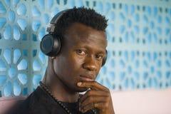 Retrato do estilo de vida do homem afro-americano fresco atrativo e pensativo novo que escuta a música nos fones de ouvido pretos imagens de stock royalty free