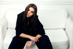 Retrato do estilo de Vogue da mulher moreno bonita em um sofá Fotografia de Stock