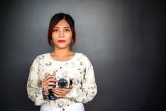 Retrato do estudante asiático bonito da moça com a câmera de bolso pequena exterior no dia Imagem de Stock