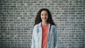 Retrato do estudante fêmea bonito que gerencie para a câmera que sorri no fundo do tijolo video estoque