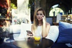 Retrato do estudante fêmea bonito que usa seu telefone de pilha ao descansar após leituras na universidade imagens de stock