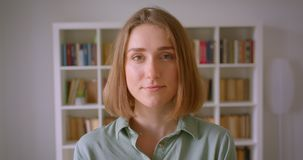 Retrato do estudante fêmea novo caucasiano que ri alegremente e felizmente na câmera em casa